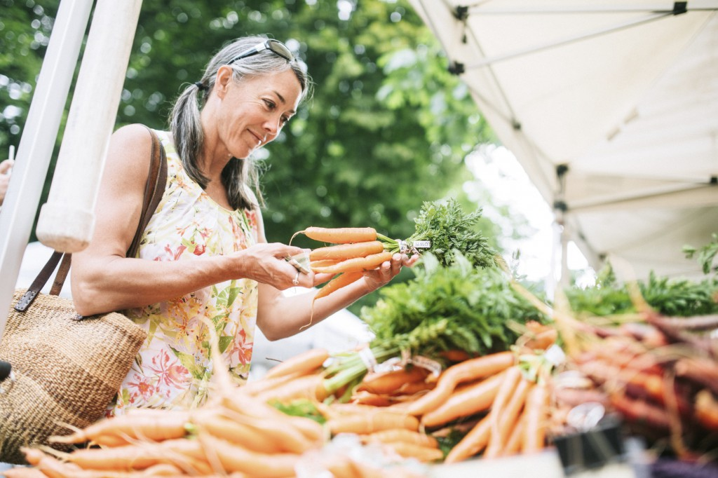 woman inspecting carrots at farmer's market
