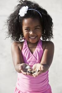 Little girl gathering shells at beach