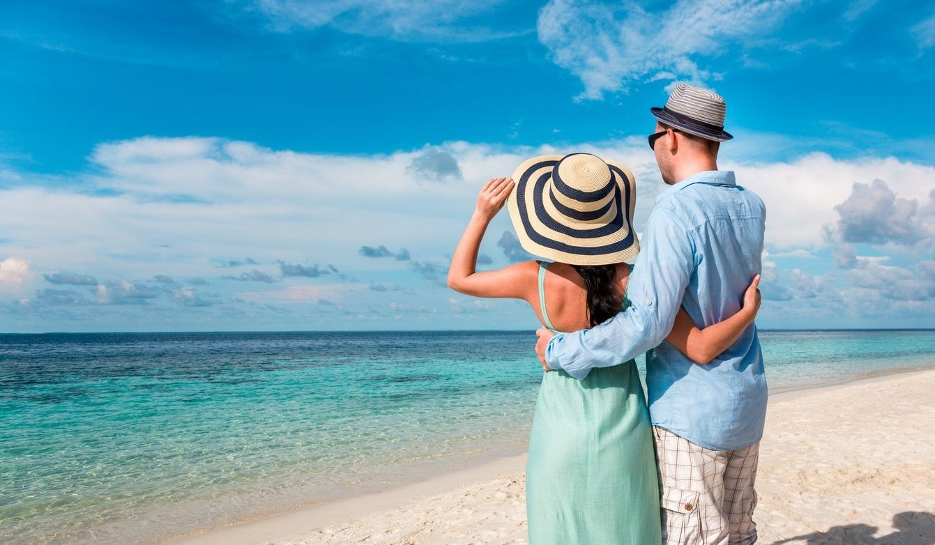 couple in resort wear on the beach